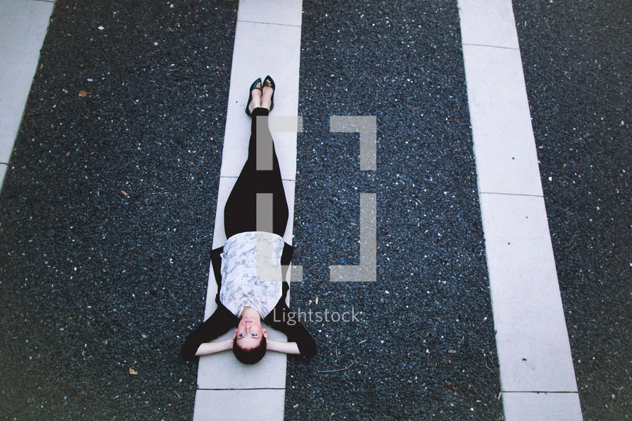 A woman lying on a white line in a parking lot.