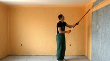 man with a roller painting a wall