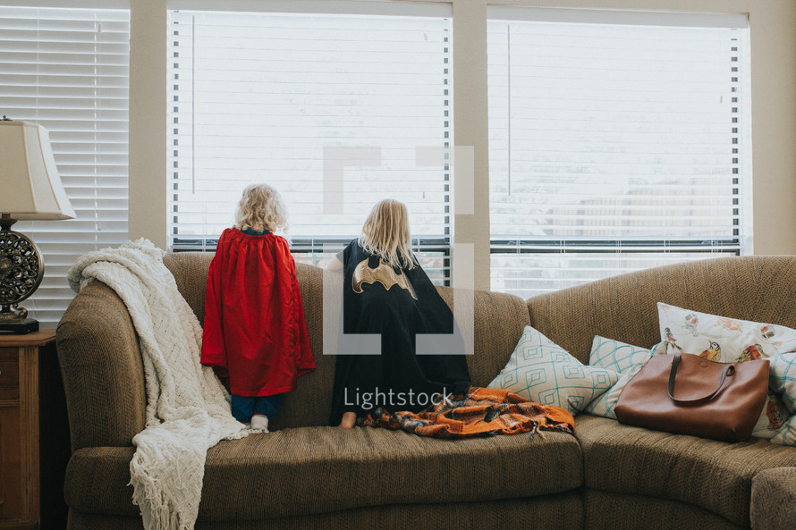 siblings in capes looking out a window standing on a couch