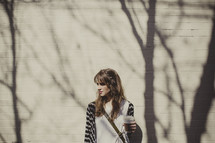 woman standing in front of a brick wall holding a coffee mug and the shadows of tree branches
