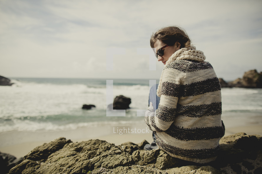woman sitting on a rock near the ocean looking to the side