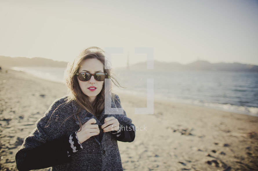 woman fastening buttons on her sweater on the beach