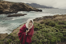 Laughing woman in red cape and head scarf holding a camera whiel standing on an oceanside hill.
