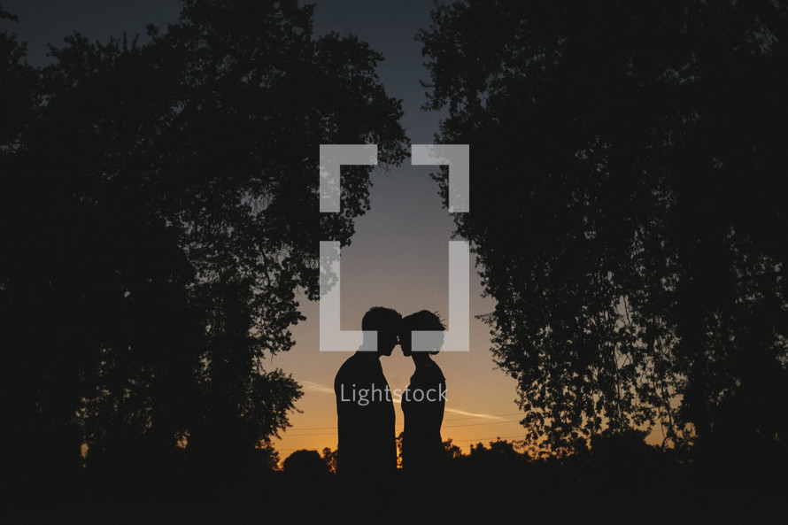 silhouette of a couple outdoors standing head to head at late sunset