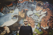 man standing in front of a graffiti covered wall