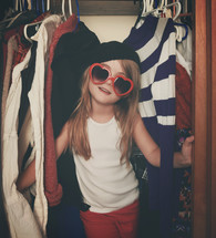 a child in a closet playing dress up