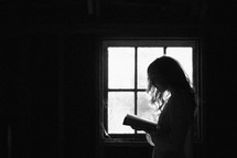 a woman reading in front of a window in a dark room