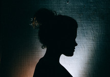 silhouette of the side profile of a woman with a hair bun