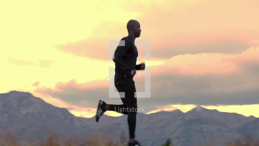 man running with mountains as a backdrop