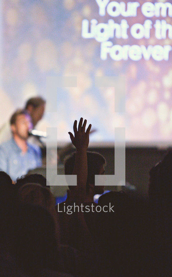Silhouette of audience with hands raised at a Christian conference.