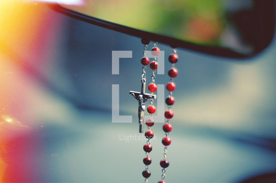 rosary hanging from a rearview mirror