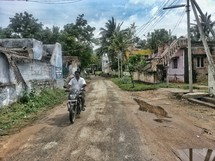 man on a dirt bike on a dirt road in a village