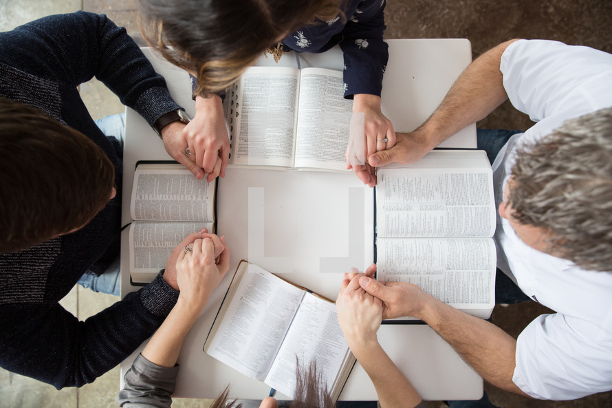Study group sitting at a table holding hands in prayer