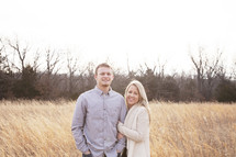 couple standing together in a field of tall grasses