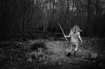 girl walking in a forest holding a stick