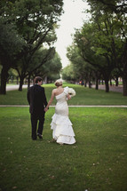 A bride and groom walking together in the grass