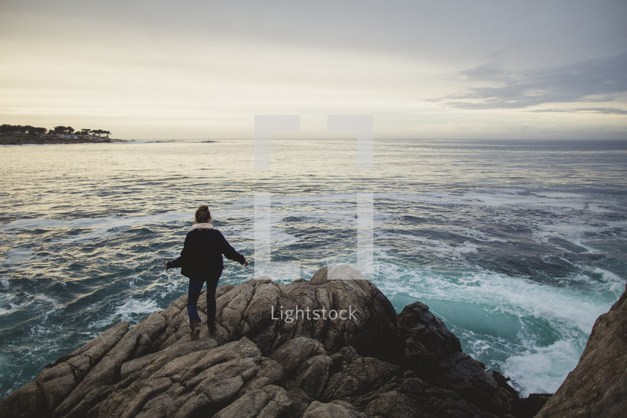 woman standing on a rock near the ocean
