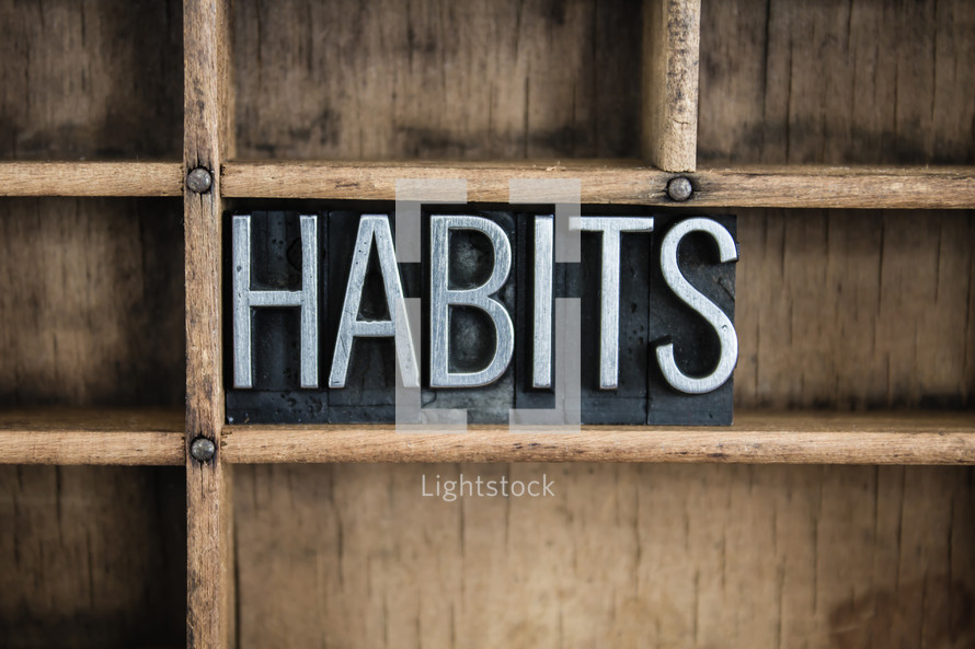 word habits in blocks on a bookshelf