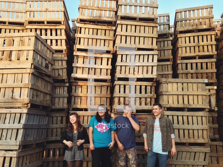young adults standing in front of wood crates