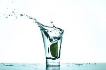 Splashing water in a shot glass with a lime.