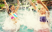 girl children splashing in a pool