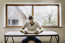 a man sitting at a desk reading a Bible with a farm scene in the window behind him