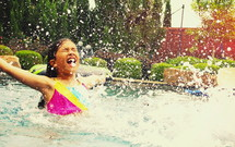 girl child splashing in a pool