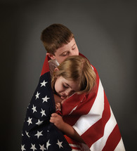 children wrapped in an American flag