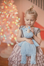a little girl holding a stuffed animal in front of a Christmas tree