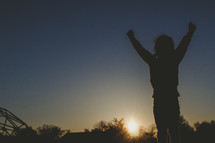 silhouette of a girl with raised hands on a playground
