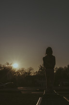 silhouette of a girl standing outdoors in her front yard