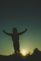 a girl child playing outdoors at sunset
