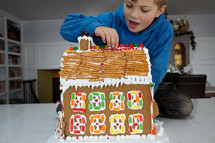 a boy decorating a gingerbread house