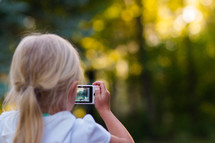 a girl child taking a picture with a cellphone