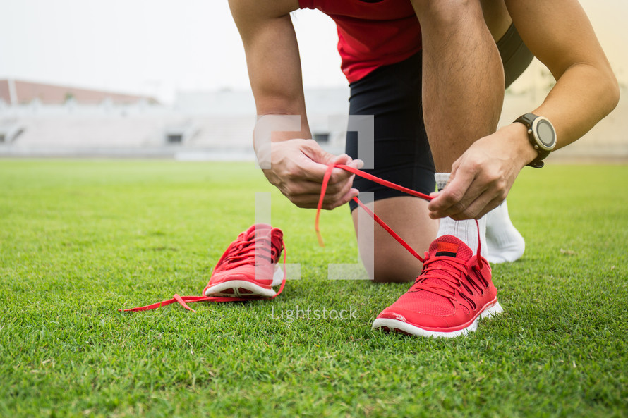 an athlete tying his shoes