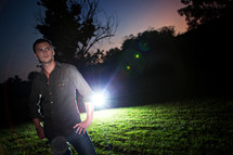 A man standing in a field with a light behind him