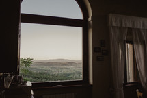 view of hills and mountains out a window in Italy