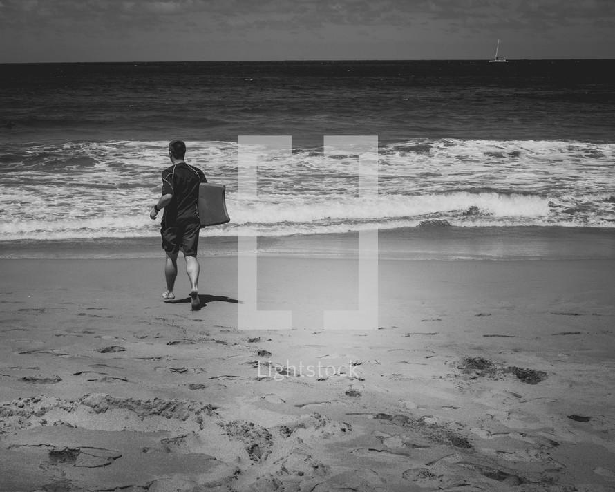 man walking on a beach holding a boogie board