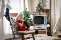 a child sitting in a chair at Christmas time