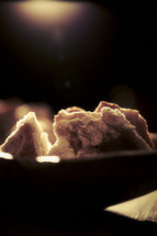 A light shines on pieces of bread in a bowl.