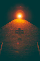 light over a cross on an exterior wall of a church