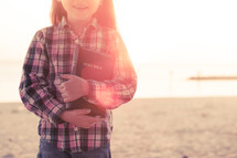 young girl happy, smiling, standing on the beach holding her bible at sunset, sunflare