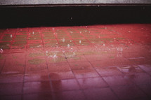 Rain drops falling on red tile.