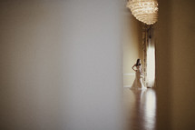 A bride standing next to the window in her wedding dress
