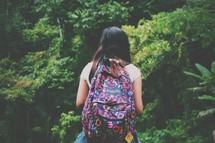 a teen girl with a backpack outdoors in a forest