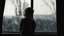 toddler boy looking out a window at falling snow