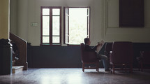 a man reading a newspaper in a waiting room