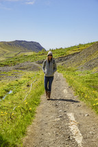 a woman walking on a dirt path in Iceland