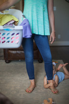 a mother holding a laundry basket and child clinging to her leg