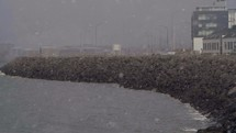 snow falling over a harbor in Iceland